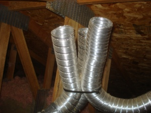 Three bathroom fans exhausting into an attic